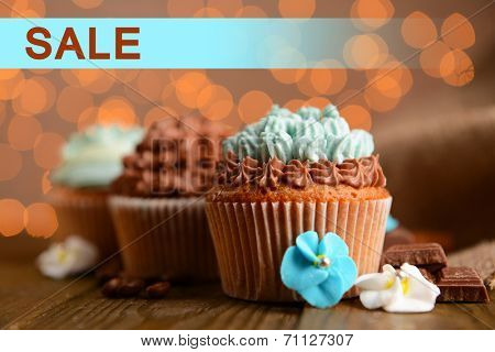 Concept of discount. Tasty cupcakes with butter cream on lights background