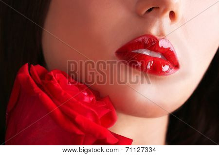 Woman's red lips and rose on dark background