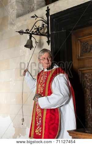 Catholic priest entering the church and ringing the bell for the beginning of mass
