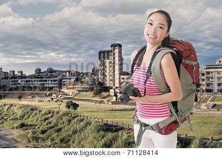 Happy smiling Asian young female backpacker with camera in the city.