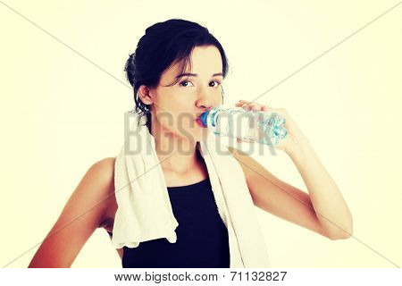 Young fit woman drinking mineral water after fitness exercise