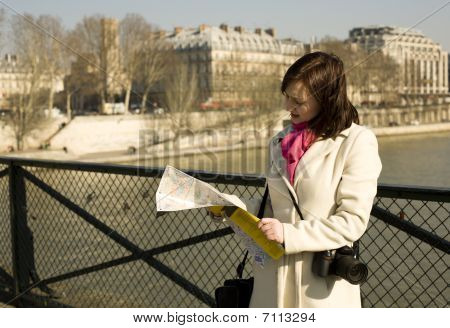 Getting Lost In Paris. Beautiful Woman With Map On A Parisian Bridge