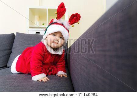 Baby girl with christmas dressing and creeping on sofa