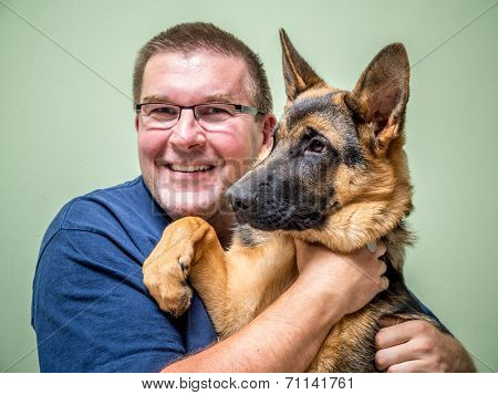 Happy young man posing with its German shepherd pet