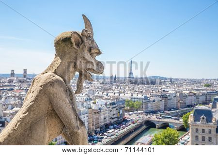 Gargoyle Stryge and demon at Notre Dame of Paris overlooking the skyline at a summer day (Selectice focus at Gargoyle)