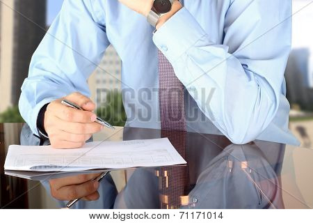 Businessman  Doing Business, Sitting At His Desk In The Office, Analyzing  Data In  Documents