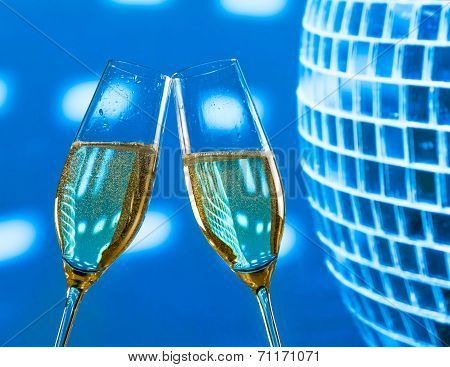 A Pair Of Champagne Flutes With Golden Bubbles Make Cheers On Sparkling Blue Disco Ball Background
