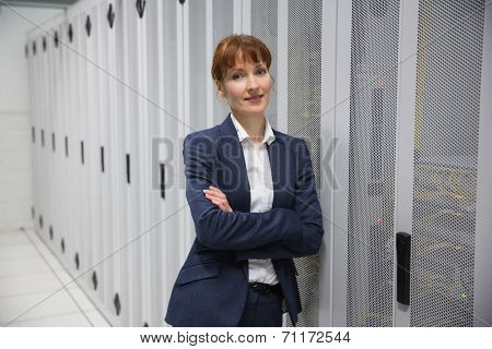 Pretty computer technician looking at camera in large data center