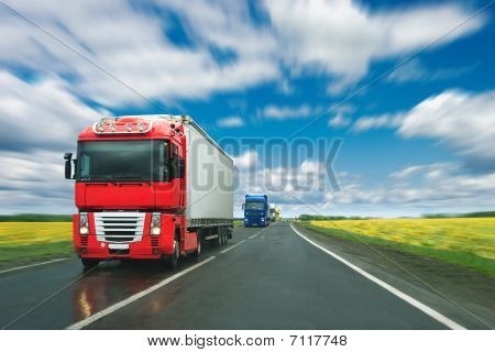 Trucks At Country Road At Sunny Day