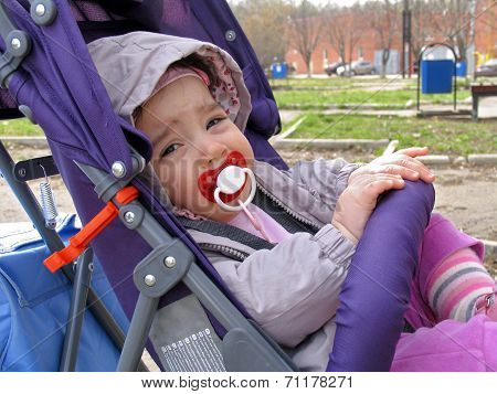 Small Child With Pacifier Sitting In Wheelchair