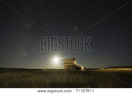 Ranch house with Moon lighting the sky.