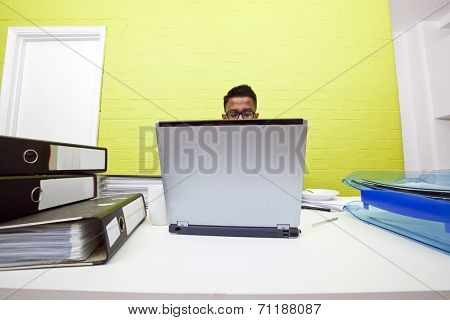 Mans head poking out over top of laptop