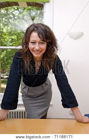 Happy businesswoman leaning on table looking at camera