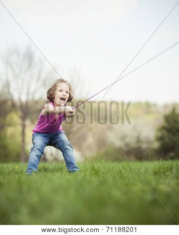 Young girl playing tug of war