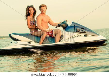 Multi ethnic couple sitting on a jet ski