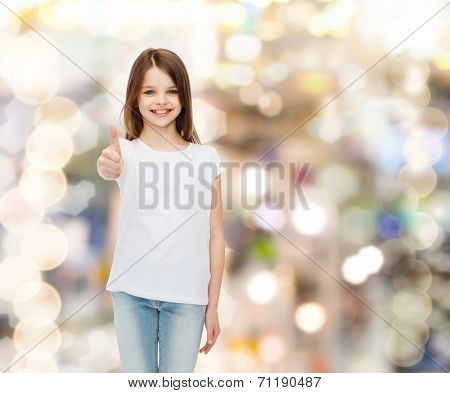 advertising, childhood, gesture, holidays and people - smiling girl in white t-shirt showing thumbs up gesture over sparkling background