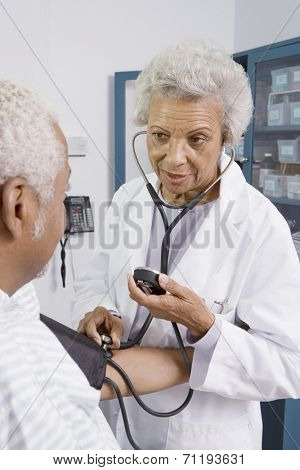 Senior medical practitioner takes blood pressure
