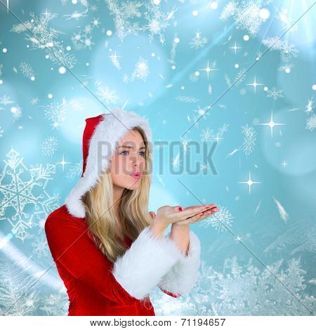 Pretty girl in santa outfit blowing against blue snow flake pattern design