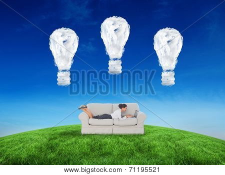 Business woman lying on couch against cloud light bulbs