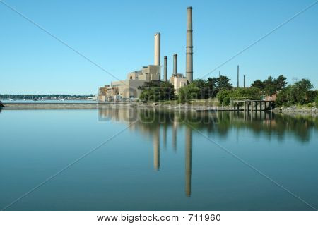Reflection Of A Power Station In The Quiet Waters Of A Cove Off The New England Coast