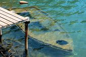 picture of loveless  - Old rowing boat sunken under water at a wooden jetty - JPG