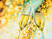 picture of flute  - a pair of champagne flutes with golden bubbles make cheers on golden light background with space for text - JPG