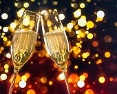 picture of champagne color  - two champagne flutes with golden bubbles make cheers on colorful light bokeh background with space for text - JPG