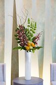 stock photo of greenery  - Floral arangement with Cymbidium and James Storey orchids Hydrangea Curly willow Yellow pin cushion protea and greenery in white cylinder vase and two beige chairs - JPG