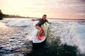 pic of watersports  - Young woman surfboarding at summer resort - JPG