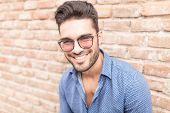 stock photo of shaved head  - closeup picture of a happy smiling young casual man with glasses leaning against brick wall  - JPG