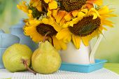picture of pitcher  - Beautiful sunflowers in pitcher with cups and pears on table on bright background - JPG