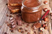 stock photo of chocolate fudge  - Sweet chocolate cream in jar on table close - JPG