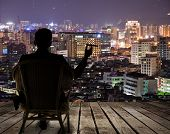 stock photo of city silhouette  - Silhouette of businessman sit on chair and hold a cigar and looking at the city in night - JPG