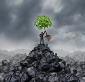 foto of waste management  - Green businessman concept as a man on top of a mountain heap of garbage holding up a green leaf tree with roots as an environment and conservation icon for waste management or a new healthy beginning - JPG