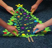 image of multicultural  - Community Christmas concept as a group of multicultural children drawiing a decorated pine tree on the floor using chalk as a winter holiday symbol for cooperation and working together to celebrate a time of giving - JPG