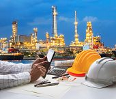 stock photo of chimney  - engineering working on computer tablet against beautiful oil refinery background - JPG