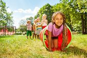 foto of crawling  - Kids play with tube on the lawn with little blond beautiful black girl with African brides crawling out and her friends standing in the queue - JPG