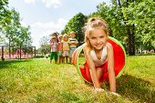 picture of crawling  - Group of children play with tube on the lawn with nice Caucasian boy crawling out of pipe with smile and her friends standing in the queue - JPG