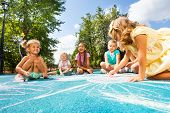 picture of playground  - Group of little kids drawing with chalk on the playground in the park - JPG