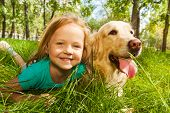 foto of dog park  - Funny wide angle portrait of happy smiling little girl and her happy golden retriever dog pet laying in the grass of sunny summer park - JPG