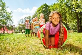 stock photo of crawl  - Kids play with tube on the lawn with little blond beautiful black girl with African brides crawling out and her friends standing in the queue - JPG
