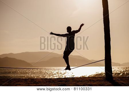 Teenage Balancing On Slackline With Sea View
