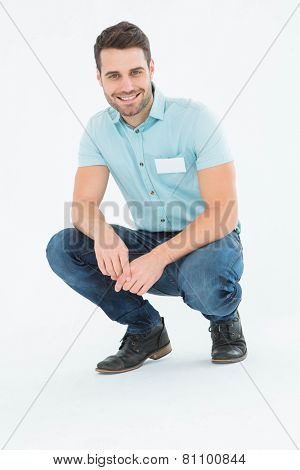 Full length portrait of handsome delivery man crouching on white background