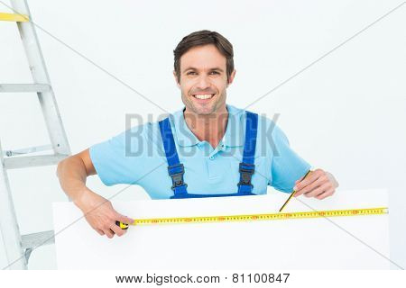 Portrait of happy carpenter measuring blank bill board over white background