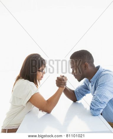Irritated business couple arm wrestling at desk on white background