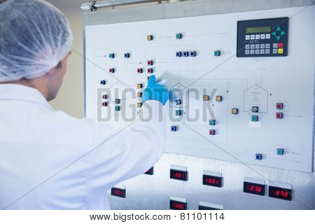 Scientist using the machine and pressing on buttons in the factory