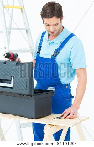 Handsome carpenter removing tools from box over white background