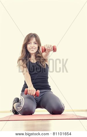 Athletic Girl With Weights Or Red Dumbbells Wearing Sports Clothing