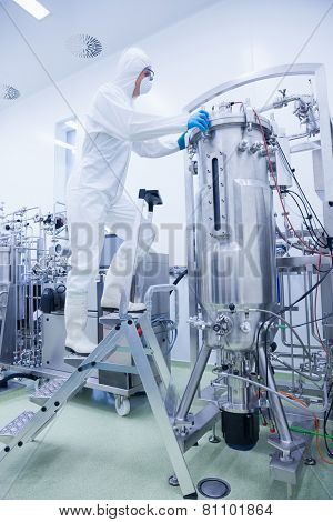 Scientist in protective suit standing on ladder in the factory