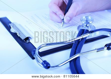 Woman filling medical history on light background